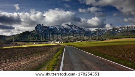 Charming village and snowy mountains - stock photo