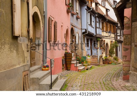 Charming village in Alsace with colorful old exposed timber buildings and cobblestone street - stock photo