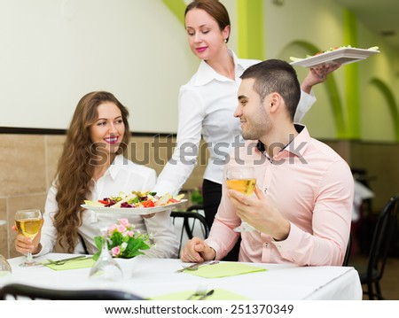Charming waitress serving meal to visitors table - stock photo