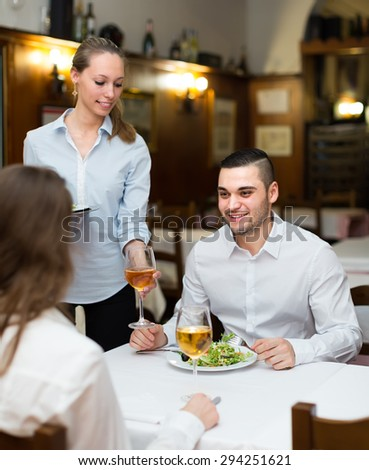 Charming waitress with prepared meal at attendee table - stock photo