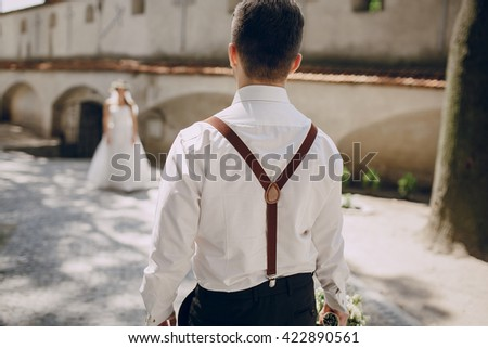 charming wedding couple in wreaths and suspenders - stock photo