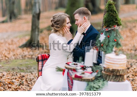 Charming wedding couple softly stroking face of each other at the holiday table in autumn forest