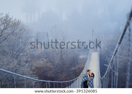 Charming wedding couple wrapped in blanket softly kiss on the suspension bridge at mountains. Autumn mountains background - stock photo