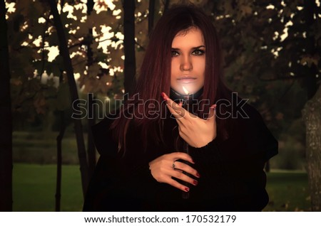 charming witch with candle - stock photo