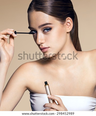 Charming woman applying mascara / photos of appealing brunette girl on beige background - stock photo