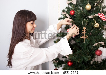 Charming woman decorating the Christmas tree with balls. Christmas Eve concept. - stock photo
