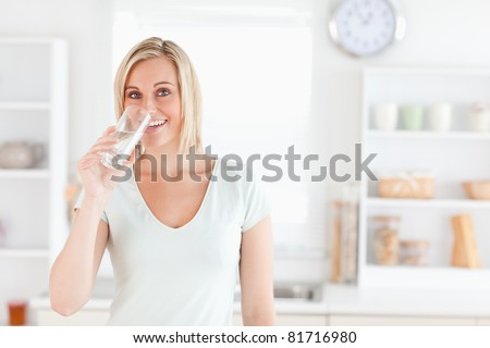 Charming woman drinking water while standing looks into camera in the kitchen - stock photo
