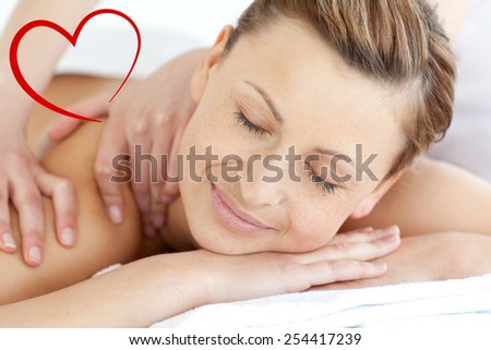 Charming woman enjoying a back massage against heart - stock photo