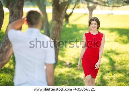 Charming woman goes on meeting to man. Romantic appointment in park - stock photo