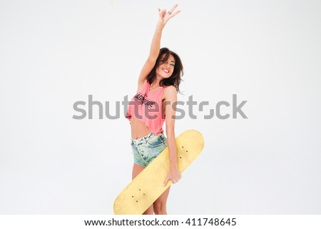 Charming woman holding skateboard and showing peace sign isolated on a white background - stock photo