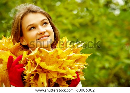 Charming woman in autumnal environment looking upwards - stock photo