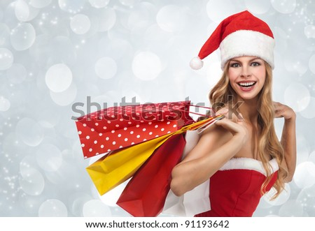 Charming woman in santa costume holding a shopping bags over winter background