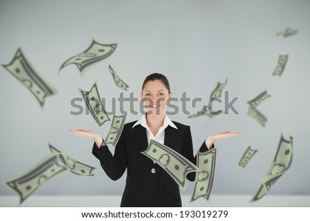 Charming woman in suit showing dollars against room with wooden floor