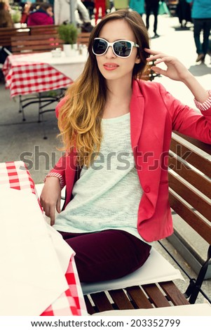 Charming woman in sunglasses at an outdoor restaurant  - stock photo