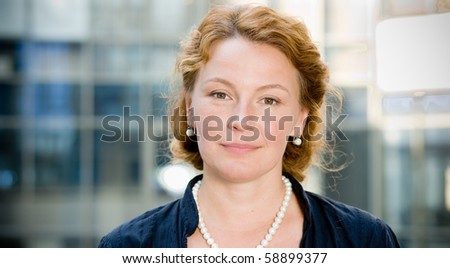 Charming woman looking at camera with a smile while standing in front of business building. Red-haired lady of middle age is a professional and confident manager. - stock photo
