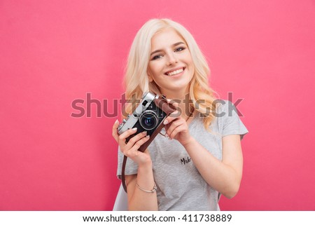 Charming woman posing with photo camera over pink background - stock photo