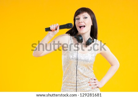 Charming woman singing with a microphone over yellow background - stock photo