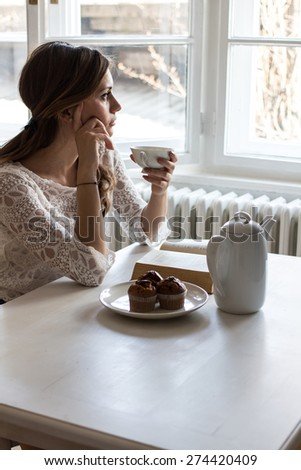 Charming woman sitting by wooden table and drinking coffee - stock photo