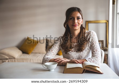 Charming woman sitting by wooden table and reading book.Blur and grain added for artistic impression. - stock photo