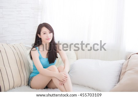 Charming woman Smile to you and she sit on the sofa at home, asian girl