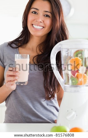 Charming woman using a blender while holding a drink in the kitchen - stock photo