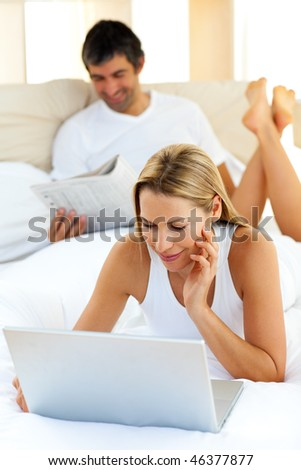 Charming woman using a laptop lying on bed at home - stock photo