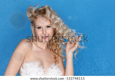 Charming woman with falling snow on blue background