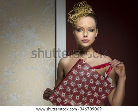 charming woman with freckles and naked shoulders posing with christmas creative make-up and golden accessories in the hair-style. Taking in the hand lovely  gift bag