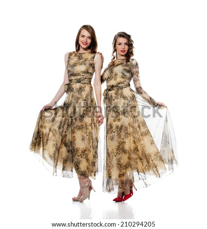 Charming women posing in dresses from same cloth - stock photo