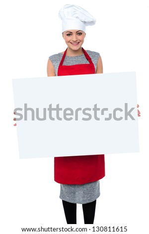 Charming young baker lady displaying a blank whiteboard. - stock photo
