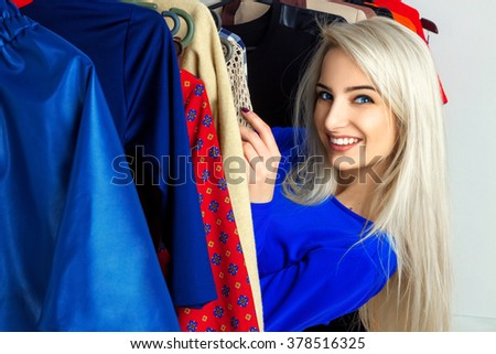 Charming young blonde girl smiling in clothing store. Happy young lady with a lot of clothes. Shopping concept. - stock photo