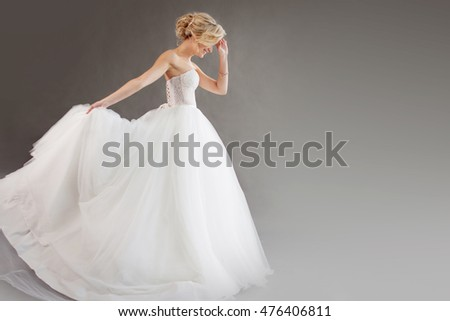 Charming young bride in luxurious wedding dress. Pretty girl in white, gray background, place for your text on the right