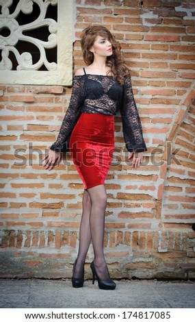 Charming young brunette woman in black lace blouse, red skirt and high heels near the brick wall. Sexy gorgeous young woman near old wall. Full length portrait of a sensual woman with long hair  - stock photo