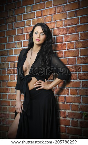 Charming young brunette woman in black near the brick wall. Sexy gorgeous young woman with low cut blouse. Portrait of a provocative woman with long hair laying agains a red brick wall - stock photo