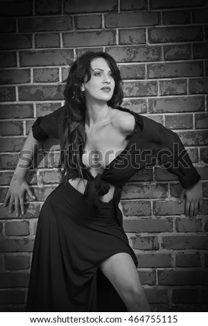 Charming young brunette woman in black near the brick wall. Sexy gorgeous young woman with low cut blouse. Portrait of a provocative woman with long hair laying against bricks wall