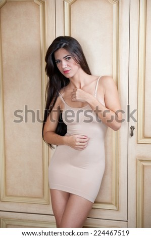 Charming young brunette woman in tight fit short nude dress leaning against wooden wall. Sexy gorgeous long hair girl near vintage wardrobe. Full length portrait of sensual female posing provocatively - stock photo