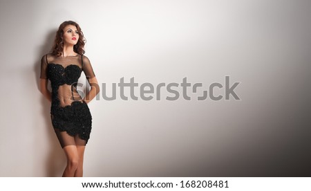 Charming young brunette woman in transparent lace black dress leaning against an white wall. Sexy gorgeous young woman near white wall. Full length portrait of a sensual woman with long hair posing - stock photo