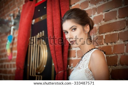 Charming young brunette woman in white lace blouse near a red brick wall. Attractive gorgeous young woman daydreaming near old wall, indoors. Beautiful portrait of a young girl with creative haircut - stock photo