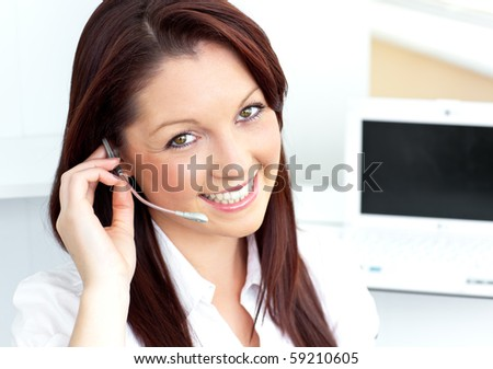 Charming young businesswoman wearing headphones smiling at the camera in her office - stock photo