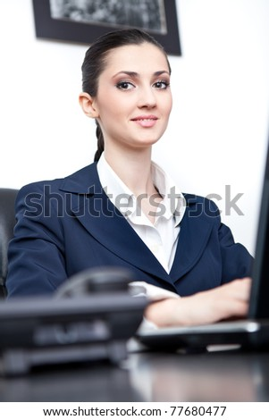 charming young businesswoman working in office, looking at camera - stock photo