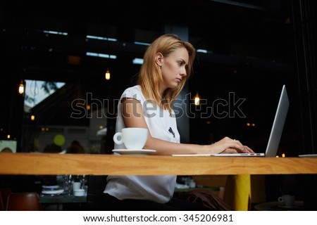 Charming young Caucasian woman work on portable laptop computer during coffee break in restaurant, gorgeous female freelancer using net-book for remote job while sitting in modern cafe bar interior - stock photo