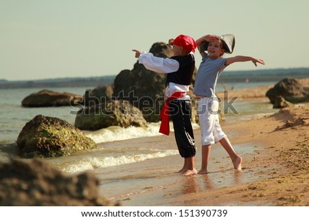 Charming young children in fancy dress playing pirates on the background of a sea landscape outdoors