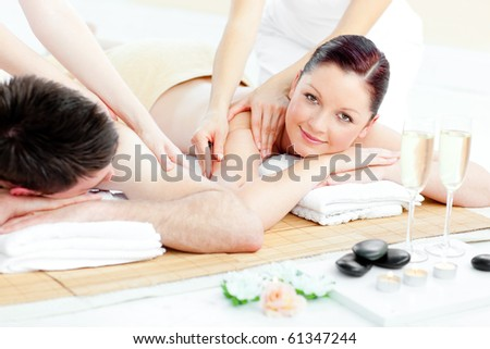Charming young couple enjoying a back massage in a spa center - stock photo