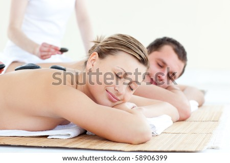 Charming young couple having a stone massage in a spa center