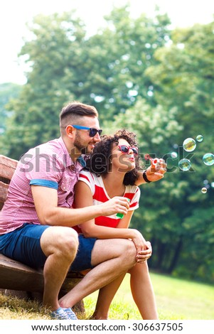 Charming young couple sitting on bench in the park and blowing bubbles. - stock photo