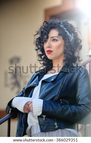 Charming young curly brunette woman with black leather jacket. Sexy gorgeous young woman with modern look. Portrait of sensual girl with voluptuous mouth wearing a gray tutu skirt, outdoor shot  - stock photo
