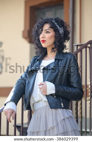 Charming young curly brunette woman with black leather jacket. Sexy gorgeous young woman with modern look. Portrait of sensual girl with voluptuous mouth wearing a gray tutu skirt, outdoor shot