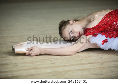 Charming young dancer doing stretching leaned over, looking at the camera. Red outfit. - stock photo