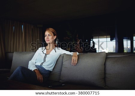 Charming young female dreaming about something good after meeting with clients in modern cozy restaurant,beautiful businesswoman think about ideas for new project while resting in coffee shop interior - stock photo