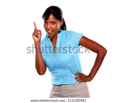 Charming young female on blue blouse pointing up and looking at you on isolated background - copyspace - stock photo